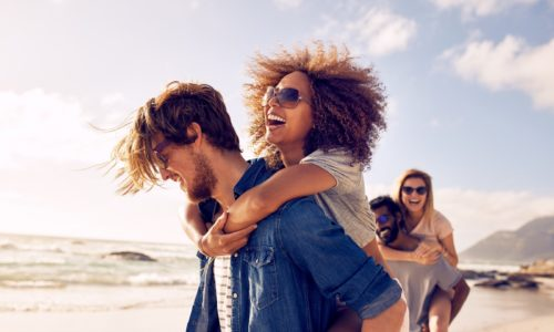 Group of friends walking along the beach with men giving piggyback ride to girlfriends. Happy young friends enjoying a day at beach.